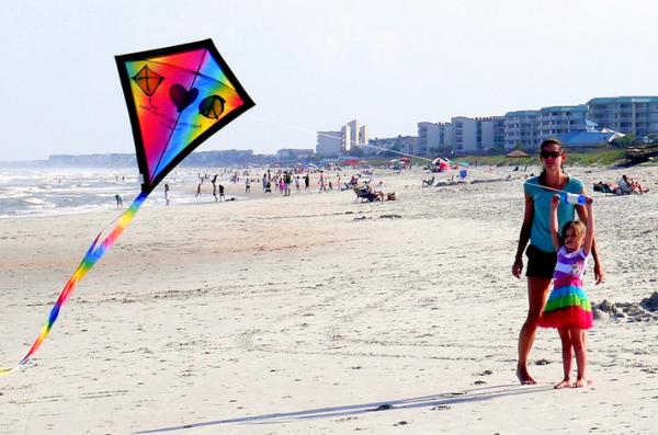 röptessetek papírsárkányt a tengerparton a gyerekekkel